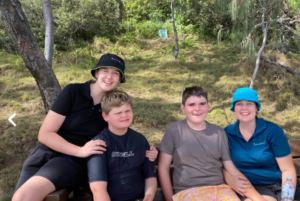 four people sitting on a bench in the bush, two ladies caring for two teenage boys with Angelman syndrome, everyone is smiling